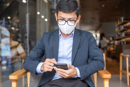 young Businessman in suit wearing surgical face mask and using smartphone, man typing touchscreen mobile phone in office or cafe. Covid-19 Pandemic, technology and New normal concept Imagens