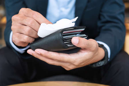 Businessman in suit cleaning money wallet by wet wipes tissue and alcohol disinfectant at office or cafe. New Normal and Clean surface concept Imagens