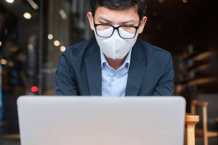 young Businessman in suit wearing surgical face mask and using laptop, man typing keyboard computer notebook in office or cafe. Imagens