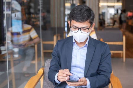 young Businessman in suit wearing surgical face mask and using smartphone, man typing touchscreen mobile phone in office or cafe.