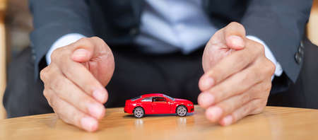Businessman hand cover or protection red car toy on table. Financial, money, refinance and Car insurance concept Imagens