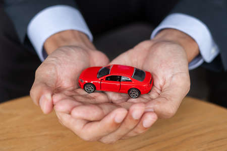Businessman hand holding red car toy on table. Financial, money, refinance and Car insurance concept