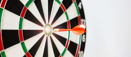 Red dart hitting a target on center of Bullseye or Dartboard. Business, competition, goal, success and marketing concept