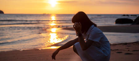 Silhouette of young woman against beautiful sunset at the beach. Stockfoto