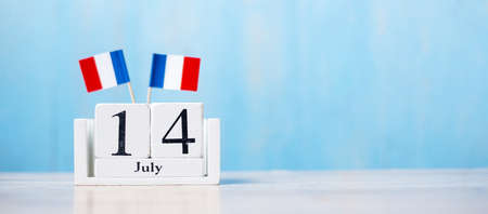 Wooden calendar of July 14th with miniature France flags. French National Day, Bastille Day and happy celebration concepts