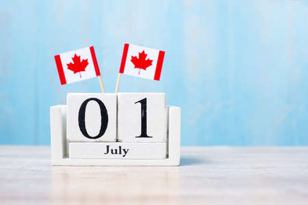 Wooden calendar of July 1st with miniature Canada flags. Canada Day  and happy celebration concepts