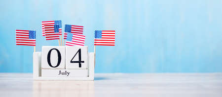 Wooden calendar of July 4th with miniature United States of America flag on wood background. Independence day and nation Holiday concept