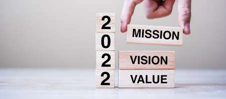 Businessman hand holding wooden cube with text 2022 Mission, Vision and Value on table background. Resolution, strategy, solution, goal, business and New Year holiday concepts
