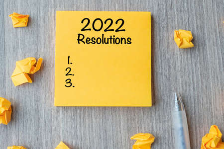2022 RESOLUTIONS word on yellow note with pen and crumbled paper on wooden table background. New start, Strategy and Goal concept Reklamní fotografie