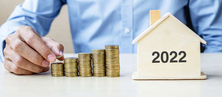 Business man hand putting golden coin on growing money stairs with 2022 wood home. Happy New Year business, investment, retirement planning, finance, Saving and New You concepts Reklamní fotografie