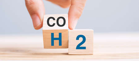 hand flipping wooden cube blocks with CO2 (Carbon dioxide), change to H2 (Hydrogen) text on table background. Free Carbon, alternative energy and global climate change concepts
