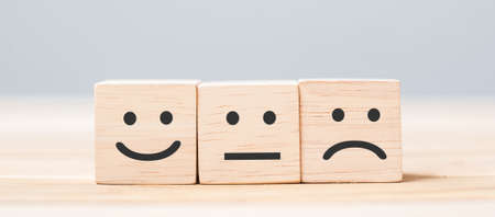 emotion face symbol on wooden cube blocks. Service rating, ranking, customer review, satisfaction and feedback concept