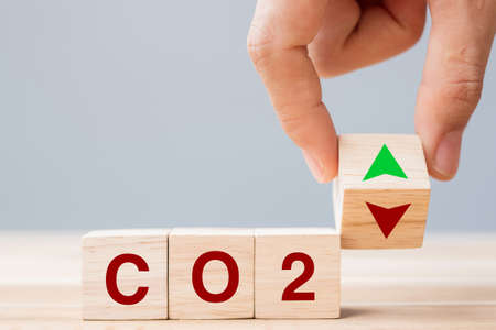hand flipping wooden cube blocks to UP and Down arrow symbol with CO2 (Carbon dioxide) text on table background. Free Carbon, alternative energy and global climate change concepts