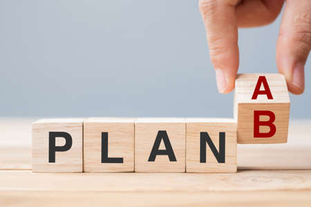 Businessman hand flipping wooden cube blocks with PLAN A change to PLAN B text on table background. strategy, leadership, management, marketing, project and Crisis concepts Reklamní fotografie