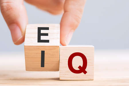 Business man hand change wooden cube block from IQ to EQ, balance between intelligence quotient and emotional intelligence concepts