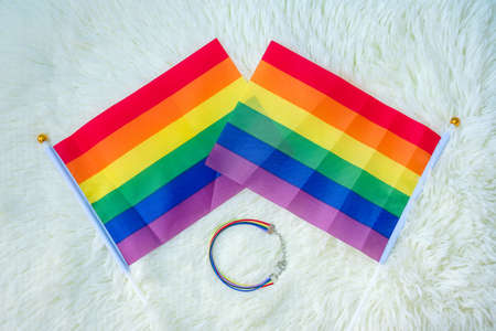 LGBTQ Rainbow flag and wristband on white background. Support Lesbian, Gay, Bisexual, Transgender and Queer community and Pride month concept Reklamní fotografie