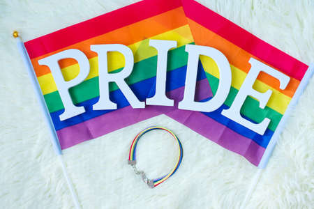 LGBTQ, Rainbow flag and wristband on white background. Support Lesbian, Gay, Bisexual, Transgender and Queer community and Pride month concept Reklamní fotografie