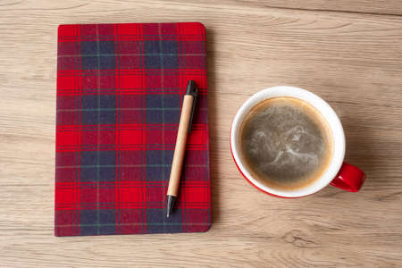 Blank notebook, coffee cup and pen on wood table. Happy New Year, Goals, Resolution, To do list, Strategy and Plan concept