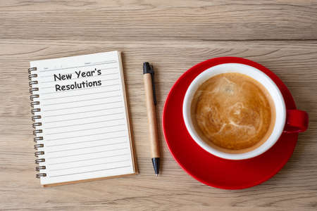 New Year Resolution with notebook, black coffee cup and pen on wood table. Xmas, Happy New Year, Goals, To do list, Strategy and Plan concept