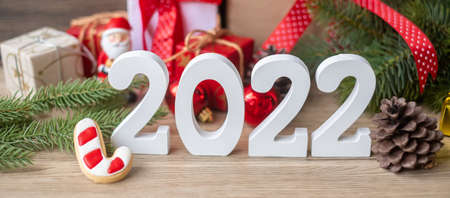 Merry Christmas and 2022 Happy New Year with decoration on table. Xmas eve, party, holiday and boxing day concept