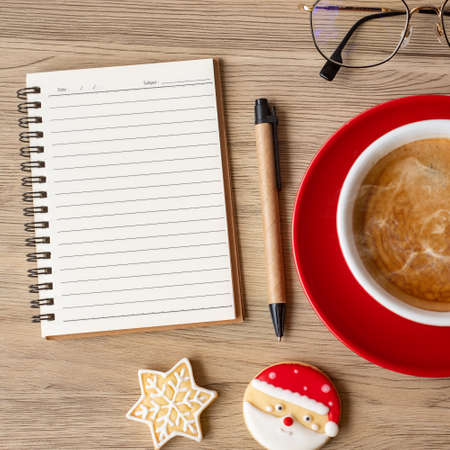 Blank notebook, black coffee cup, Christmas cookies and pen on wood table, Top view and copy space. Xmas, Happy New Year, Goals, Resolution, To do list, Strategy and Plan concept