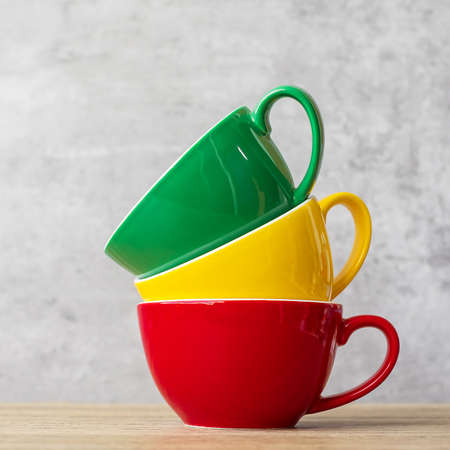 stack of colorful coffee cups on wall background at cafe. Green, yellow and red color ceramic mug on table at home. International coffee day concept