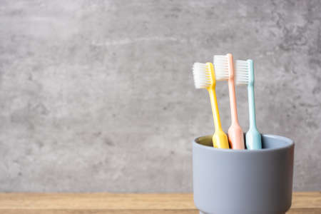 Set of Toothbrushes in cup on wall background at bathroom. World oral health day and free dental day concept
