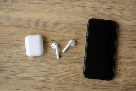 White wireless earphone or headphones on table for using with smartphone. Technology concept Stock Photo