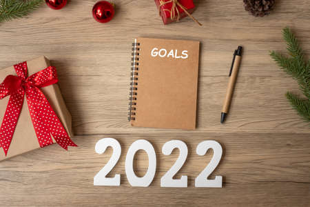 2022 GOAL with notebook, Christmas gift and pen on wood table. Xmas, Happy New Year, Resolution, To do list, start, Strategy and Plan concept Stock Photo