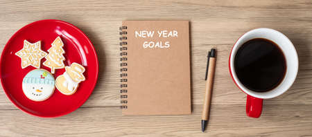 New Year Goal with notebook, black coffee cup, Christmas cookies and pen on wood table.  Xmas, Happy New Year, Resolution, To do list, Strategy and Plan concept