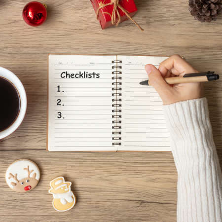 Woman hand writing checklist on notebook with black coffee cup and Christmas cookies on table. Xmas, Happy New Year, Goals, Resolution, To do list, Strategy and Plan concept