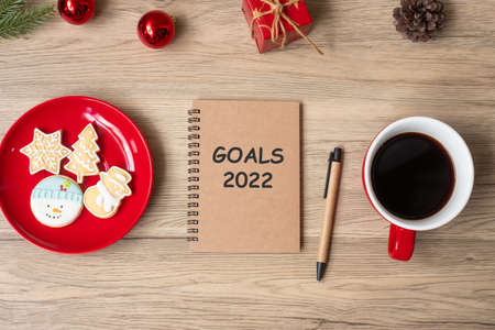 2022 GOAL with notebook, black coffee cup, Christmas cookies and pen on wood table. Xmas, Happy New Year, Resolution, To do list, Strategy and Plan concept