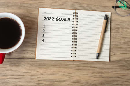 2022 GOAL with notebook, black coffee cup and pen on wood table, Top view and copy space. Happy New Year, Resolution, To do list, Strategy and Plan concept