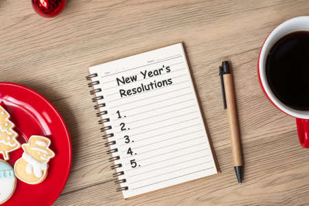 New Year Resolution with notebook, black coffee cup, Christmas cookies and pen on wood table. Xmas, Happy New Year, Goals, To do list, Strategy and Plan concept