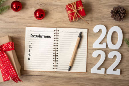 2022 Resolutions with notebook, Christmas gift and pen on wood table. Xmas, Happy New Year, Goals, To do list, start, Strategy and Plan concept