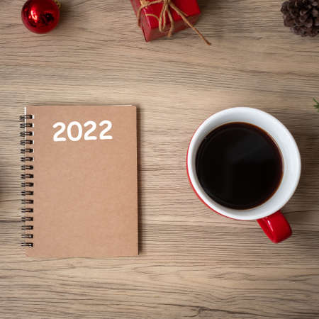 2022 notebook, black coffee cup and Christmas gift on wood table, Top view and copy space. Xmas, Happy New Year, Goals, Resolution, To do list, Strategy and Plan concept