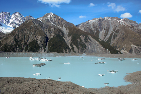 Tasman glacier lake during sunny day with icebergs on water and snowy mountains in background, in New Zealand