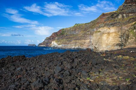 Rough coastline with dark stones on the beautiful Sao Miguel Island, Azores, Portugal