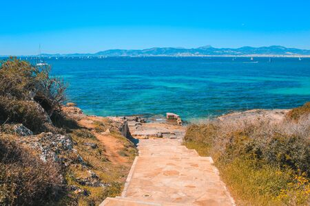 Staircase to the beach. View over beautiful coast with sailing boats in the south of Mallorca, Spain Stock Photo