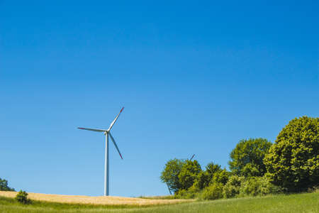 Windmills on a German green field. Wind energy theme. Wind turbines producing electricity