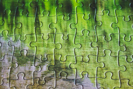 Jigsaw puzzle. Closeup of green jigsaw puzzle peices. Conceptual photo with focus on completed puzzle