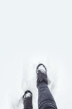 Walking on snow covered ground. Hiking boots covered in snow. Winter outdoor activity Imagens