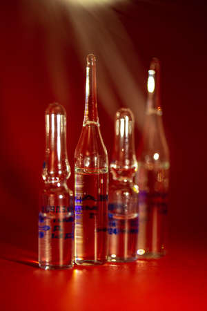 vials for vaccination against the virus on a red background.