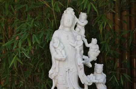 Guan Yin with childran at bambo tree in the garden  photo