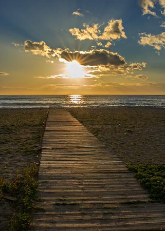 Wooden walkway on the beach at sunset Standard-Bild