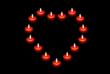 heart of red candles on a black background photo