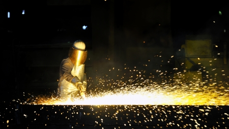 foundry: worker using torch cutter to cut through metal
