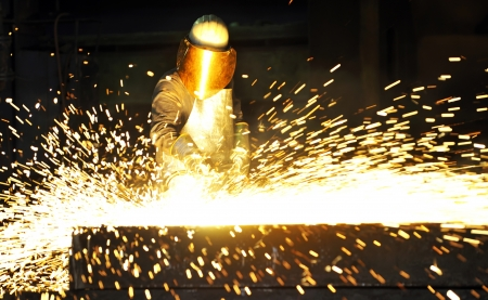 foundry: worker using torch cutter to cut through metal Stock Photo