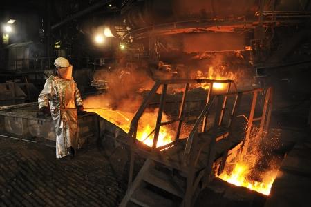 bussines: Gesmolten hete staal gieten en arbeider Stockfoto