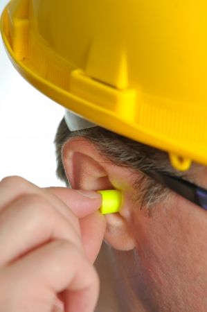 yellow earplug into the ear  Stock Photo